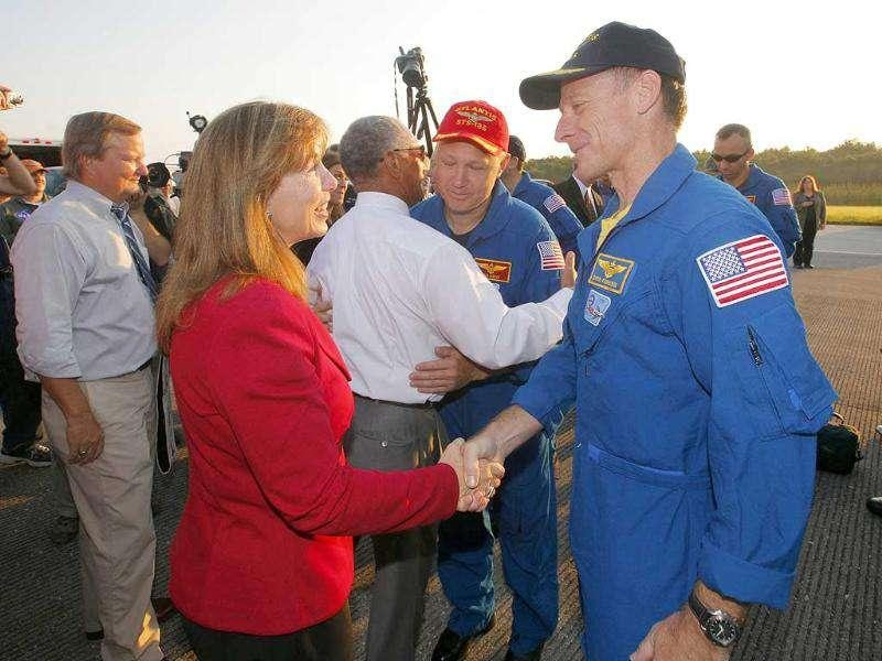 Space shuttle Atlantis mission commander Chris Ferguson (R) is greeted by Nasa deputy administrator Lori Garver after landing at the Kennedy Space Center in Cape Canaveral, Florida.
