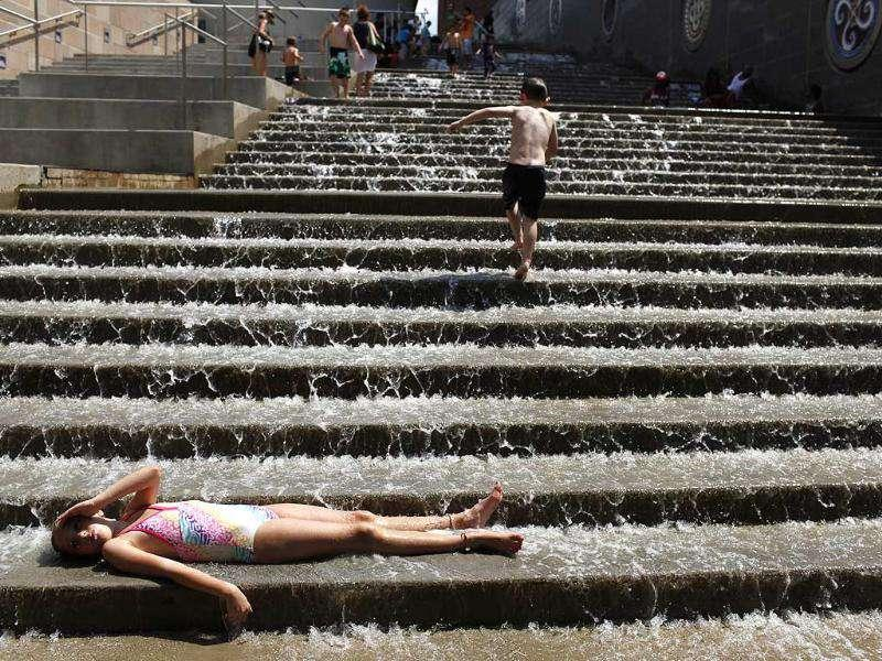 Madison Hawkins, 8, enjoys the cool water and hot sun as she lays on the steps of The Passage in Chattanooga, Tenn.