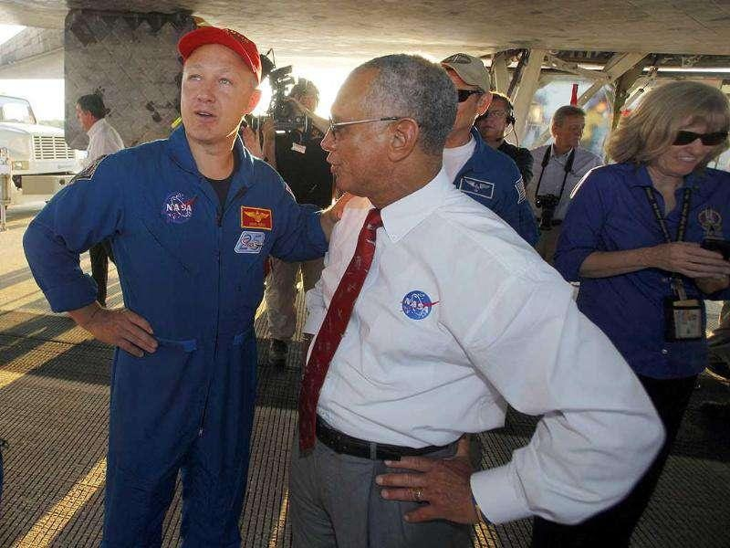 Nasa administrator Charles Bolden, right, and pilot Doug Hurley speak while walking under Space Shuttle Atlantis after landing at the Kennedy Space Center at Cape Canaveral.