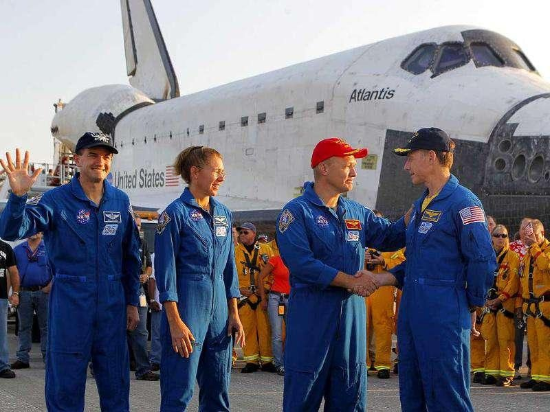 Commander Chris Ferguson, right, shakes hands with pilot Doug Hurley after landing Space Shuttle Atlantis at the Kennedy Space Center at Cape Canaveral, Florida. The landing of Atlantis marks the end of Nasa's 30 year space shuttle program.
