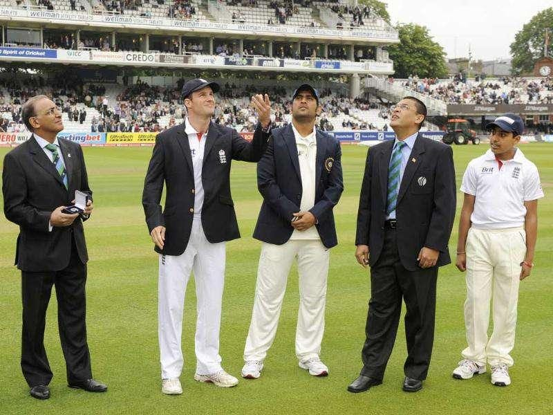England's captain Andrew Strauss (2nd L) and India's captain MS Dhoni (C) toss the coin during Day 1 of the first Test at Lord's Cricket Ground in London.