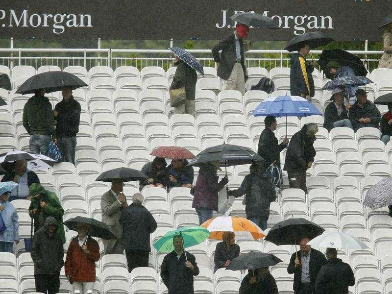 Spectators are seen under umbrellas as the Day 1 of England vs India Test match is suspended due to heavy rain at Lord's Cricket ground in London.