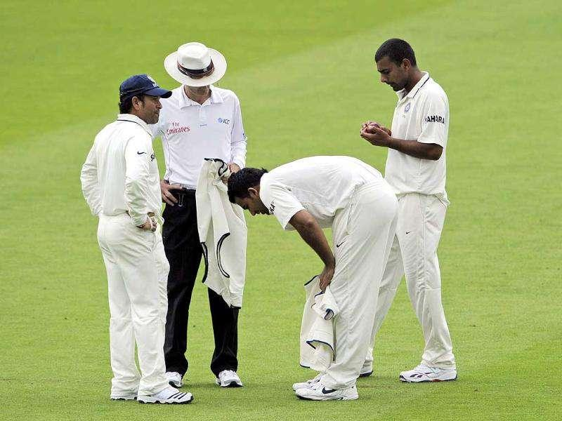 Zaheer Khan (2nd R) bends over as Sachin Tendulkar (L) and Praveen Kumar (R) look on during the Day 1 of the first Test match against England at Lord's Cricket Ground, London.