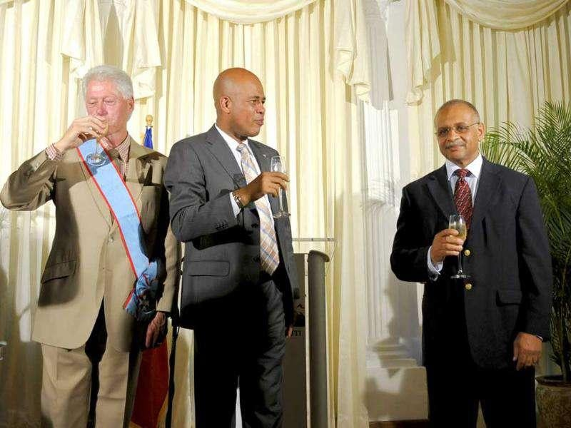 Former US President Bill Clinton (L-R), Haiti's President Michel Martelly and prime minister-designate Bernard Gousse drink champagne after Clinton was awarded the