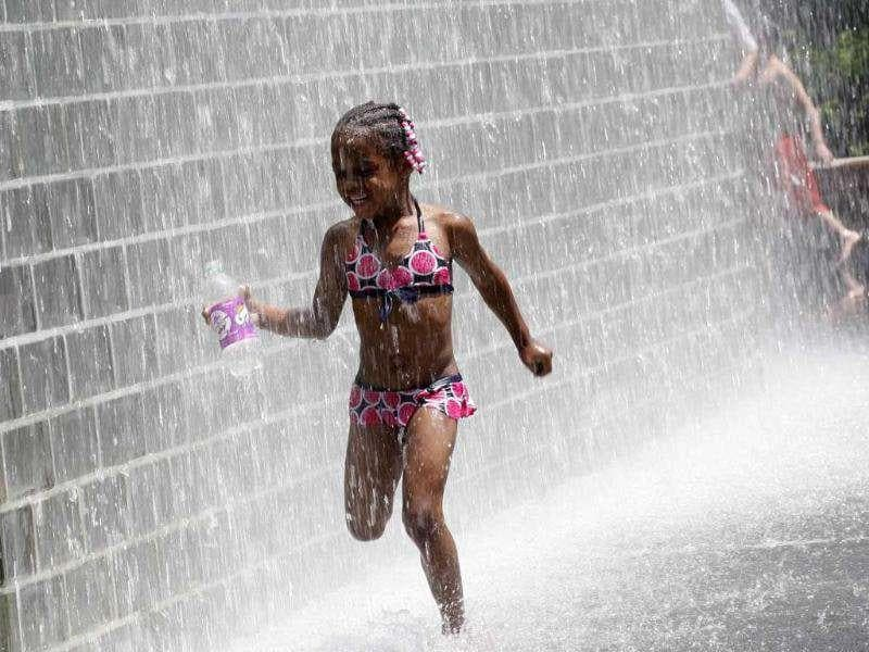 A girl cools herself at Crown Fountain at Millennium Park in Chicago. Crowds flocked to waterfronts and swimming pools on the US East Coast and in the Midwest to try to cope with a massive heat wave that has killed at least 22 people this week.