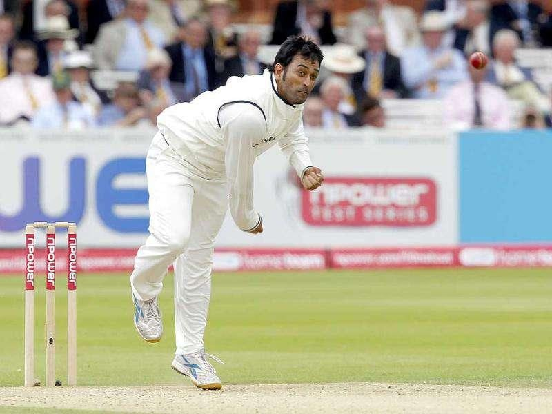 India's captain and wicketkeeper MS Dhoni bowls against England during Day 2 of the first Test match at Lord's Cricket Ground in London.
