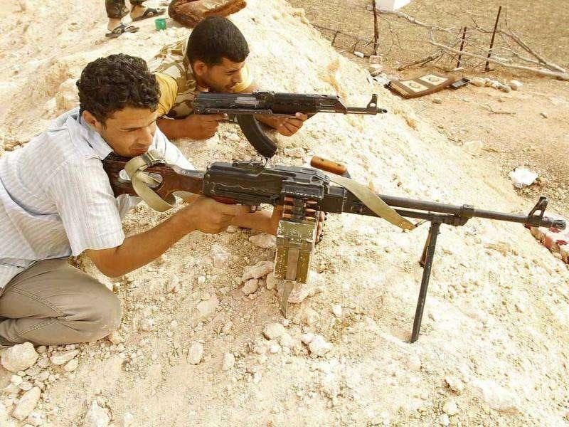 Rebel fighters with weapons are seen at their positions in the outskirts of Gawalich near Zintan.