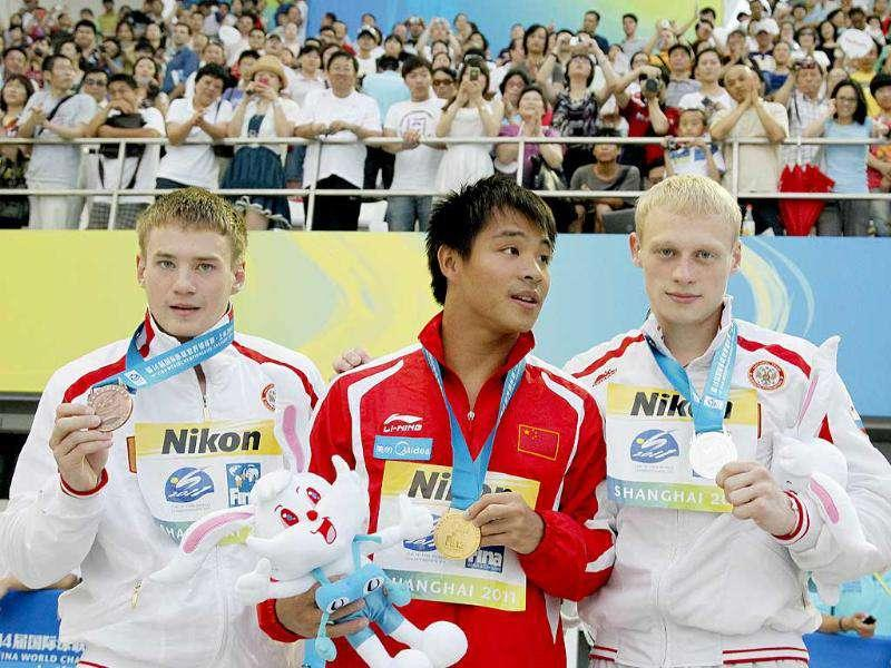 China's He Chong poses with his gold medal with Russian's Evgeny Kuznetsov, left, bronze and Ilya Zakharov silver following the men's 3-Meter Springboard final at the FINA Swimming World Championships in Shanghai.