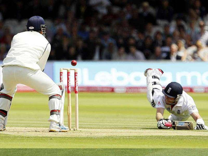 Ian Bell dives to make the crease as wicketkeeper Mahendra Singh Dhoni attempts to run him out during the second day of the first Test at Lord's Cricket ground in London.