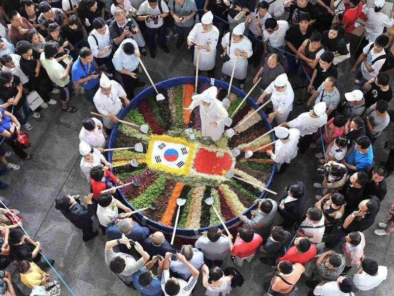 Visitors take pictures as chefs prepare to mix a giant bowl of the traditional Korean dish