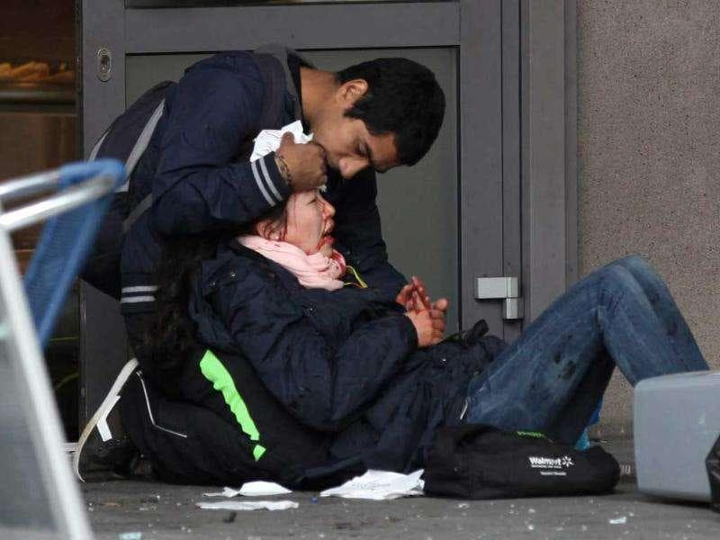 A passer-by comforts an injured woman after a powerful explosion rocked central Oslo.