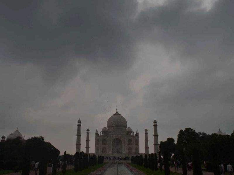 Dark monsoon clouds hovering over the majestic Taj Mahal monument in Agra.