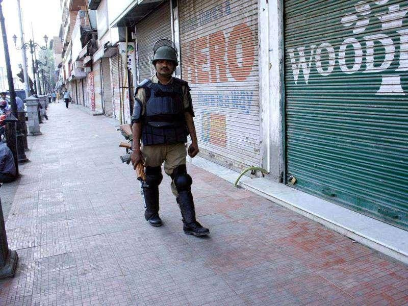 CRPF personnel patroling a market past closed shops at Srinagar during a bandh call given by the separatists against rape of a woman allegedly by two security personnel in south Kashmir district of Kulgam.