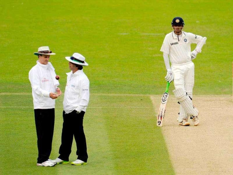 Rahul Dravid waits for his next batting partner as umpires Billy Bowden (L) and Asad Rauf talk during the first cricket Test match at Lord's in London.