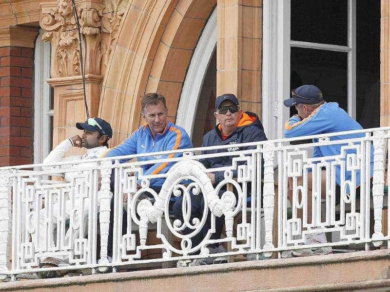 India's coach Duncan Fletcher (2nd R) watches his team from a balcony during their match against England on Day 3 of the first Test match at Lord's Cricket Ground in London.