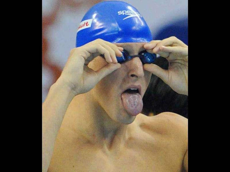 Britain's Adam Brown adjusts his glasses as he competes in the heats of the men's 4x100-metre freestyle swimming event in the FINA World Championships at the indoor stadium of the Oriental Sports Center, in Shanghai.
