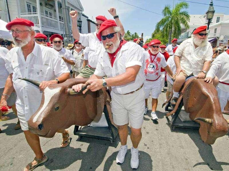 Ernest Hemingway look-alikes ride and push fake bovines during the