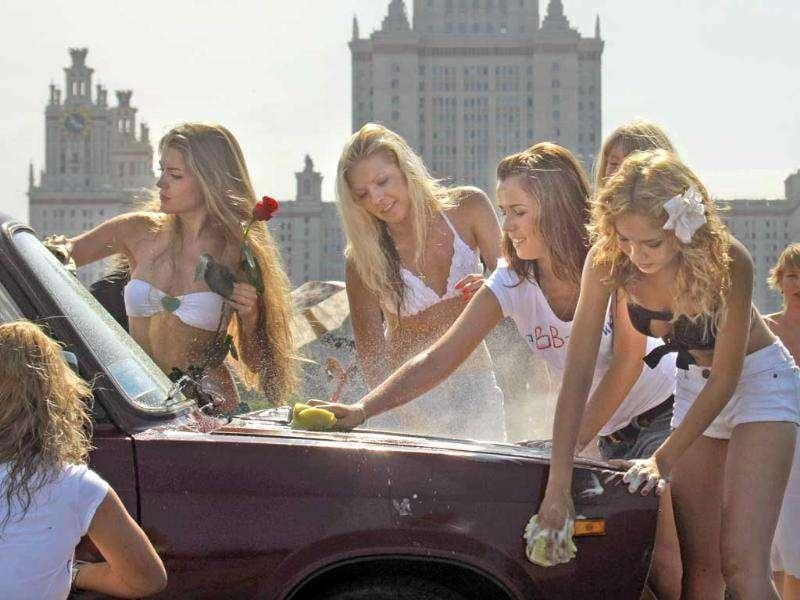 Activists supporting Russian Prime Minister Vladimir Putin wash a Russia-made car to show their support of domestic car industry, with Moscow State University in the background, in Moscow, Russia.