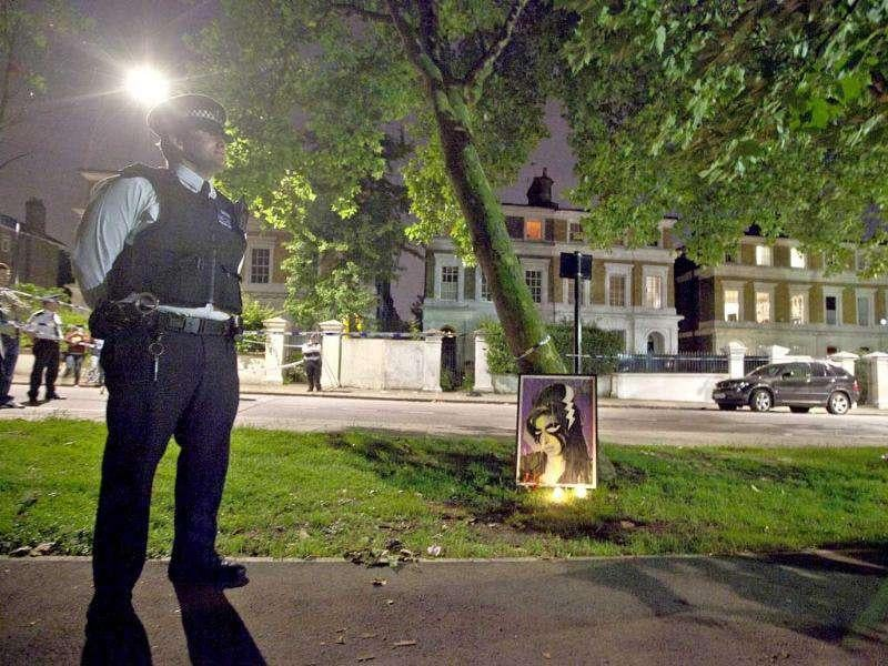 A policeman stands by a memorial opposite the home of British singer Amy Winehouse in Camden Square, London, following her death.