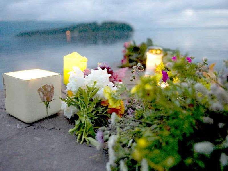 The Utoeya island, 40km south west of Oslo is seen in the background as flowers and candles are laid in memory of the victims of July 22 shooting spree on the island.