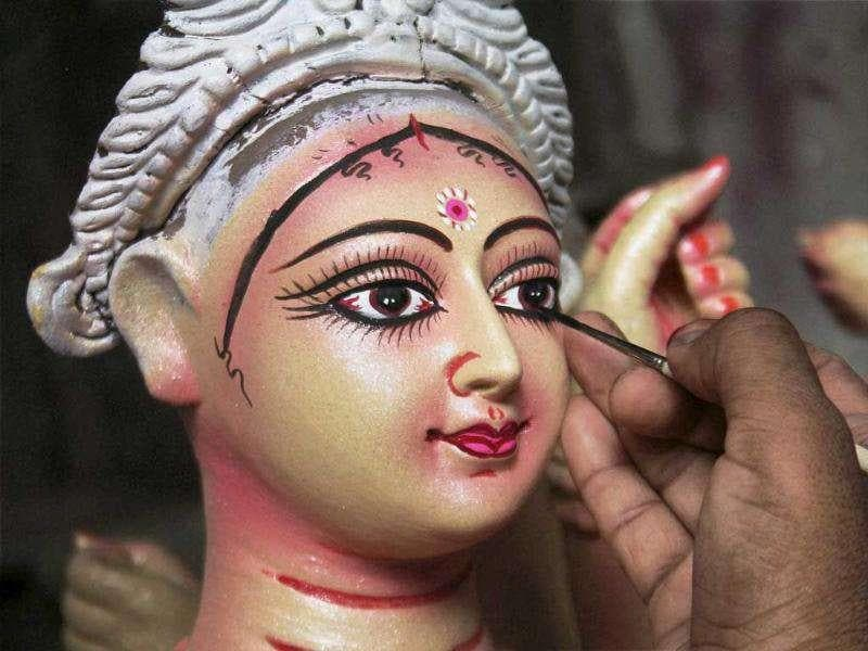 An artist gives finishing touches to an idol of Goddess Durga ahead of Durga Puja festival in Surat.