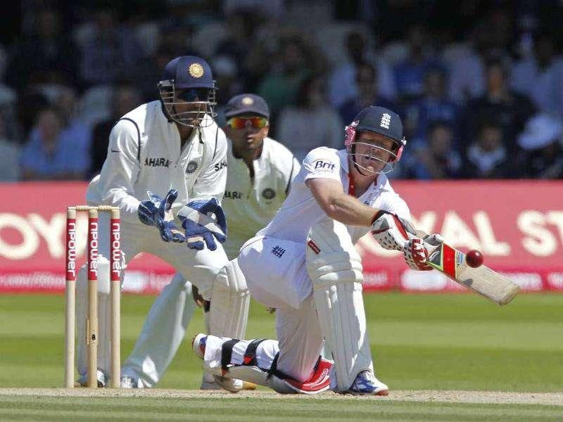 England's Eoin Morgan (R) hits a shot watched by India's captain and wicketkeeper MS Dhoni (L) during Day 4 of the first Test match at Lord's in London.