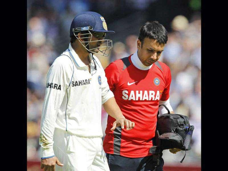 Gautam Gambhir (L) leaves the field after getting hit on the left arm by the ball whilst fielding against England during Day 4 of the first Test match at Lord's in London.