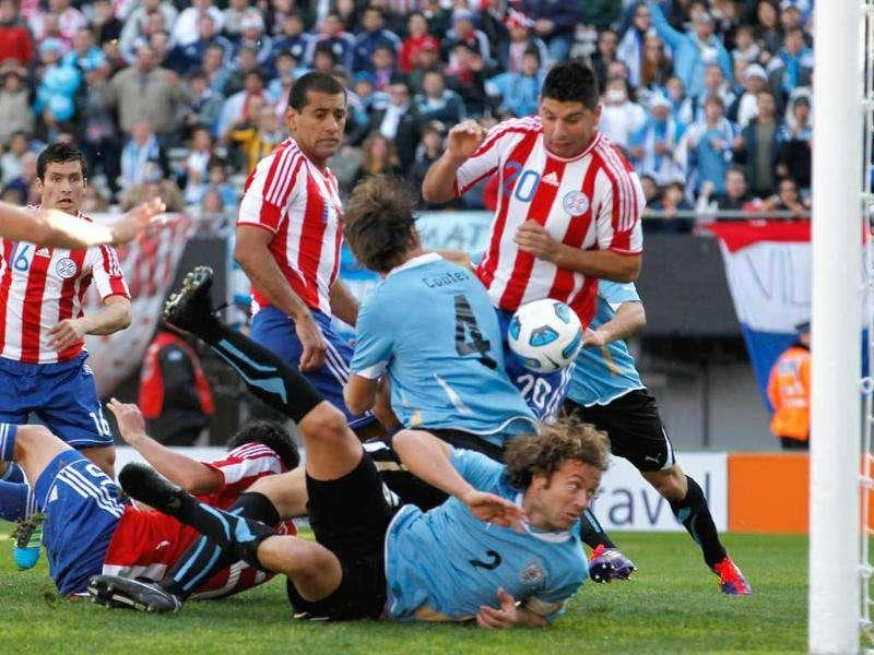 Paraguay's Nestor Ortigoza (R) stops a goal from Uruguay's Sebastian Coates (4) in their Copa America final soccer match in Buenos Aires.