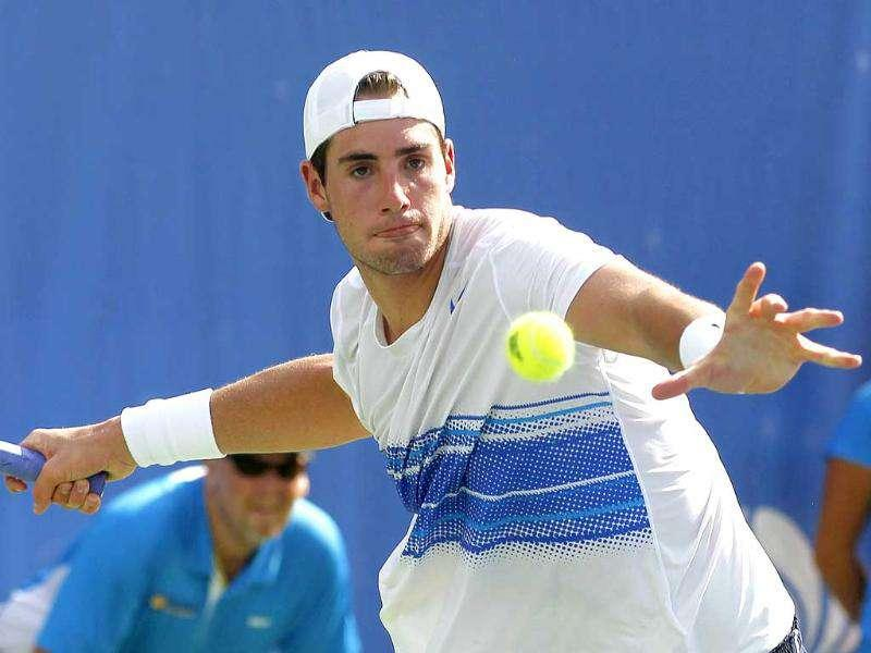John Isner returns a volley from Mardy Fish in the third set of the finals of the Atlanta Tennis championships in Norcross.