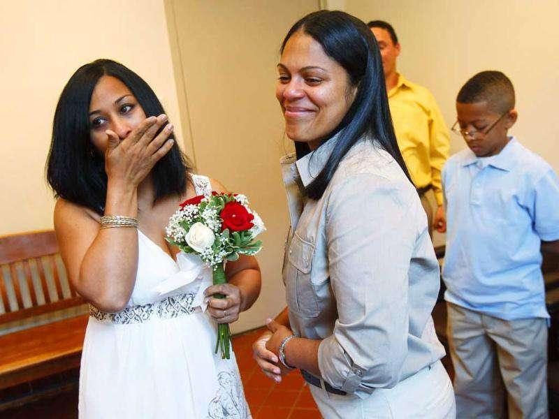 Same-sex couple Mishan Moore (L), 39, reacts as her partner Jacqueline Rodriguez, 34, looks on during their wedding ceremony at Queens Borough Hall in New York.