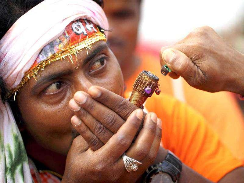 A Hindu devotee is seen while he smokes marijuana after taking part in a