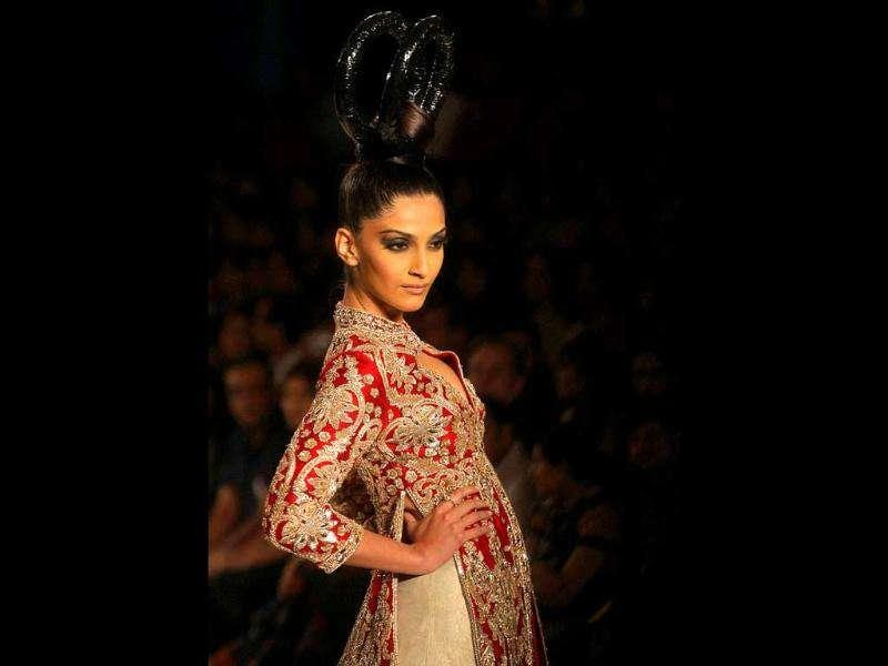 Sonam looked stunning dressed in a white lehenga with red-golden border and backless overcoat with embellished gold work.