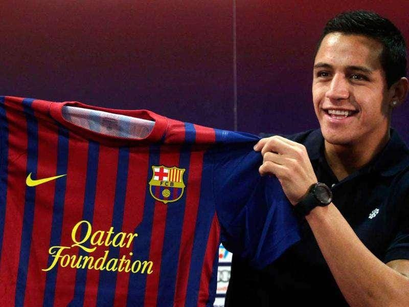Barcelona's new soccer player Alexis Sanchez from Chile poses with his new club jersey after signing a five-year contract with the Spanish and European champions.