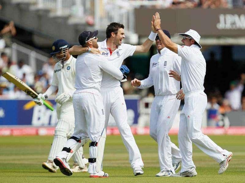 England's James Anderson (C) celebrates with captain Andrew Strauss (at right) after taking the wicket of Rahul Dravid during the fifth day of the first Test at Lord's in London.