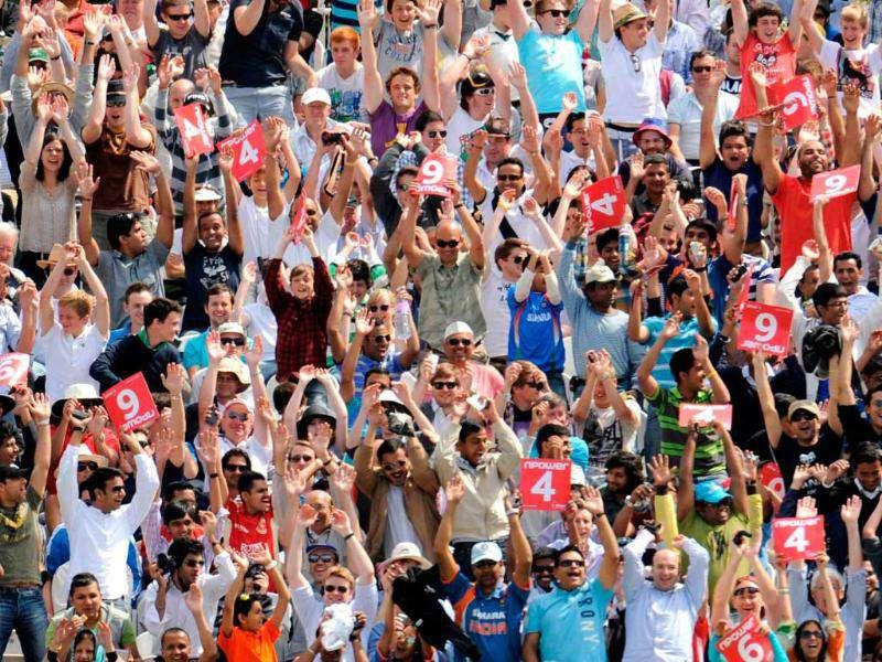 Spectators in the Compton stand raise their arms during a Mexican wave during the final day of the first cricket Test match between England and India at Lord's in London.