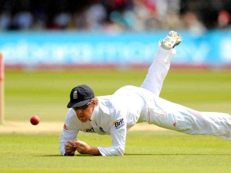 England's Graeme Swann dives to stop a ball during the final day of the first cricket Test match against India at Lord's in London.