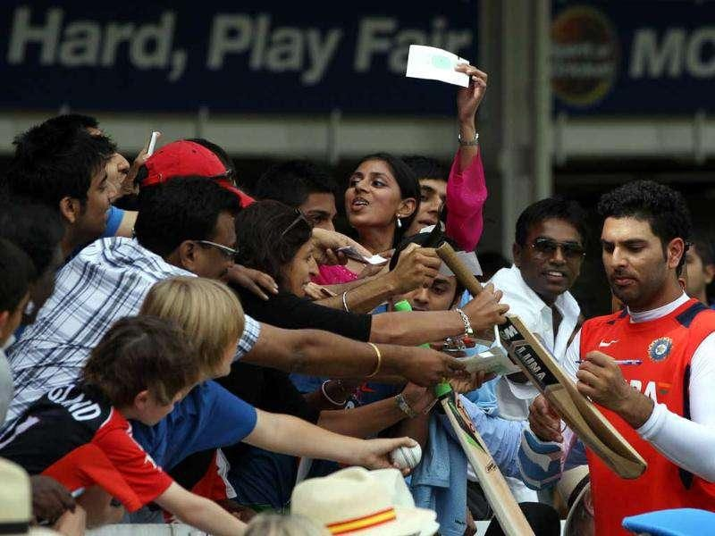 Yuvraj Singh (R) autographs a bat for cricket fans during the last day of India vs England Test match at Lord's in London.