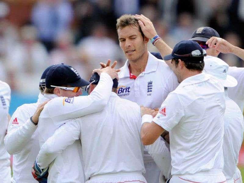 England's Chris Tremlett (centre facing) celebrates after he claims the wicket of Mahendra Singh Dhoni during the fifth day of the first Test match at Lord's in London.