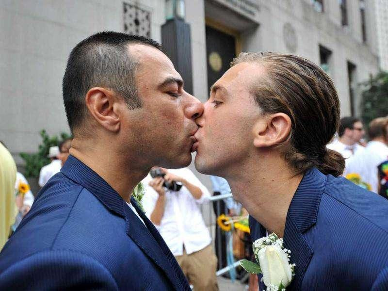 Lino Caminha Strandquist (L) and Daniel Luke Strandquist Caminha (R) kiss as they wait outside Manhattan's City Clerk's Office in order to marry in New York.