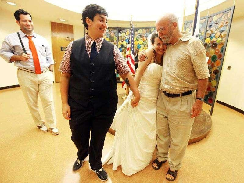 Lailah Pepe (2nd R) hugs her father David Bragin after marrying Rachel Pepe (L) in a chapel at the Brooklyn City Clerk's office in New York.