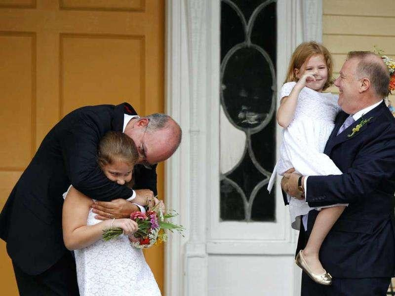 New York City's consumer affairs commissioner Jonathan Mintz (L) and a chief adviser to the mayor John Feinblatt (R) embrace their daughters Maeve (2nd L) and Georgia after being married by New York City Mayor Michael Bloomberg at Gracie Mansion in New York.