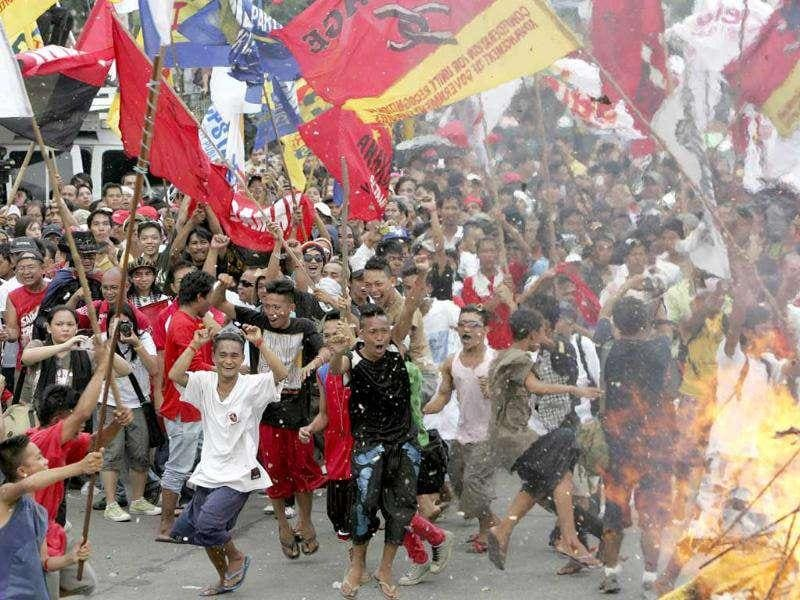 Protesters dance around a burning effigy of Philippine President Benigno Aquino III in protest.