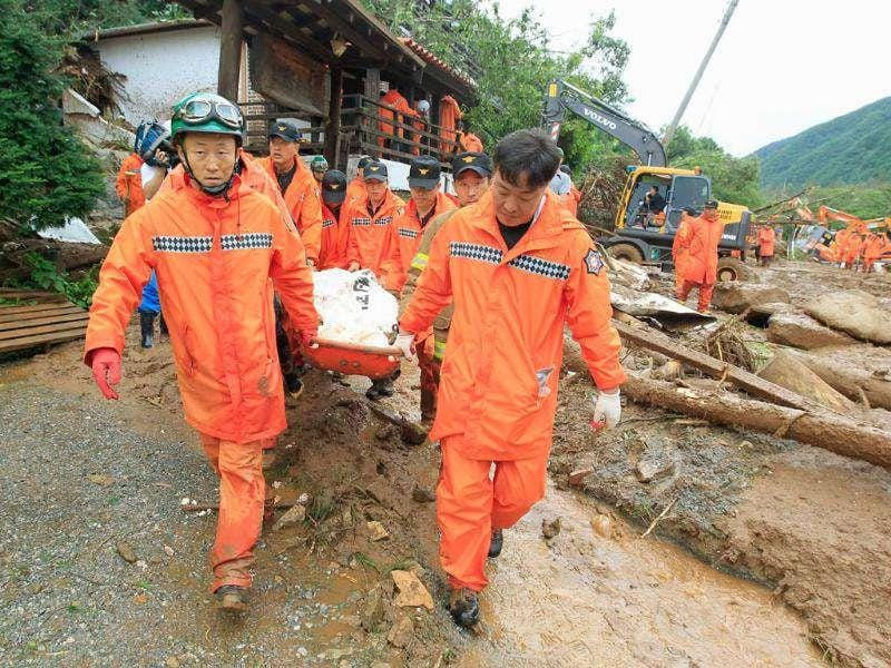 Rescue workers remove a body from a collapsed house in Chuncheon, about 100 km (60 miles) east of Seoul.