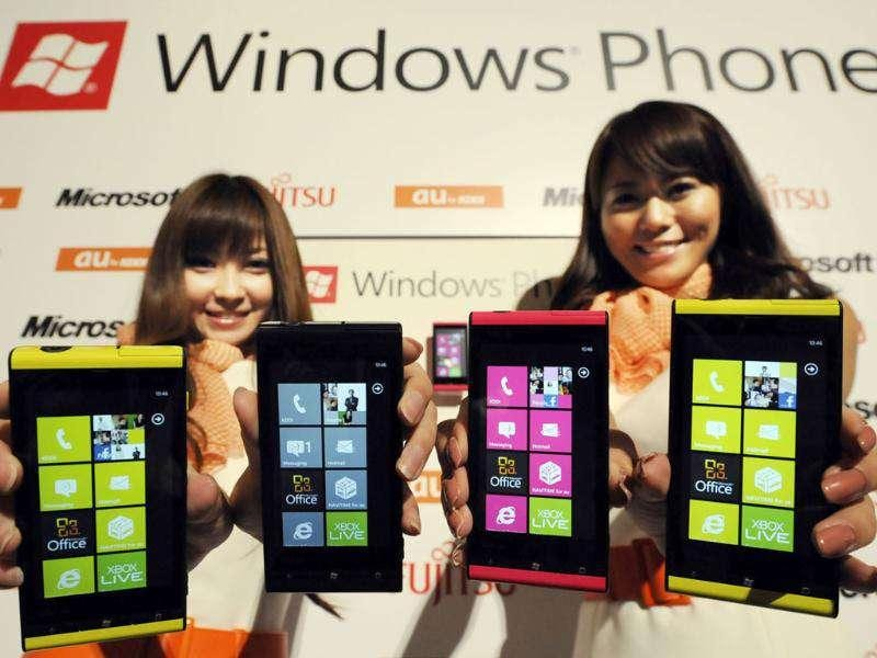 Models show off Windows Phone IS12T smartphones during its press preview in Tokyo.