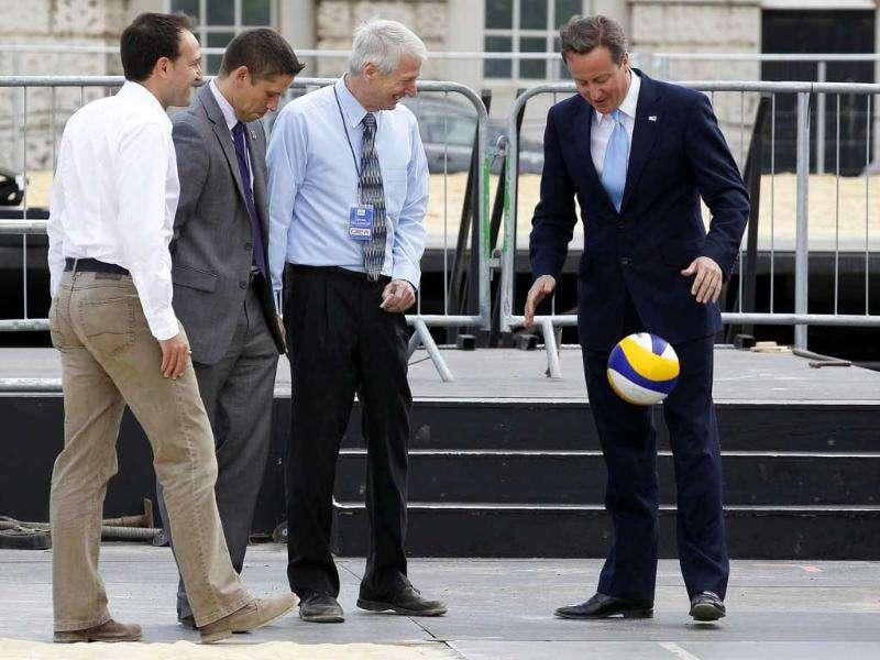 Britain's Prime Minister David Cameron (R) plays with a volleyball during a visit to the beach volleyball site for the 2012 Olympics, at Horse Guards Parade in central London, as the one-year countdown to the Games got under way.
