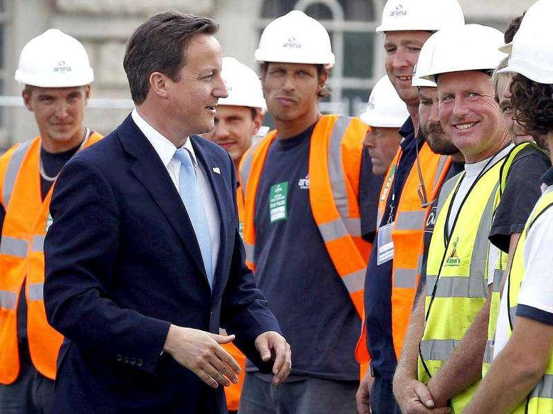 Britain's Prime Minister David Cameron (C) speaks with construction workers during a visit to the beach volleyball site for the 2012 Olympics, at Horse Guards Parade in central London.