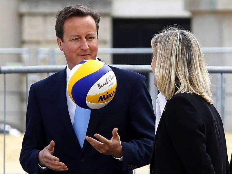 Britain's Prime Minister David Cameron (L) plays with a volleyball during a visit to the beach volleyball site for the 2012 Olympics, at Horse Guards Parade in central London.