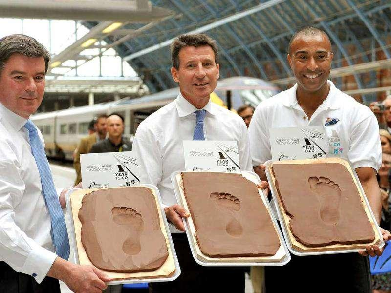 British sports and Olympic minister Hugh Robertson, left, chairman of the London 2012 Olympics Lord Seb Coe, center, and Olympic silver medallist Colin Jackson stand with clay moulds, after having made impressions of their feet, at St Pancras Railway station in central London to celebrate the one-year-to-go mark.