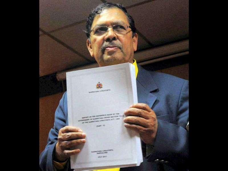 Karnataka lokayukta justice Santosh Hegde showing a copy of his report on illegal mining during a press conference in Bangalore.