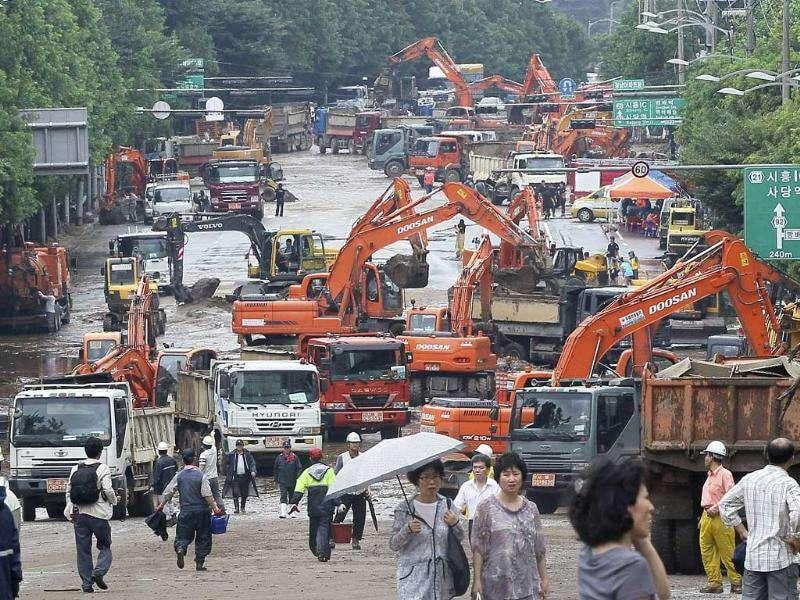 Heavy machines are brought in to restore a road damaged by a landslide in Seoul, South Korea.